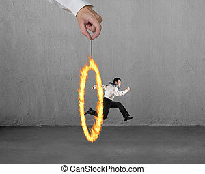 Man jumping through fire circle hand holding with concrete wall