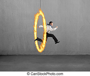 Man jumping through fire hoop with concrete wall