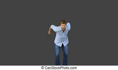Man jumping to show his triumph on grey screen in slow...