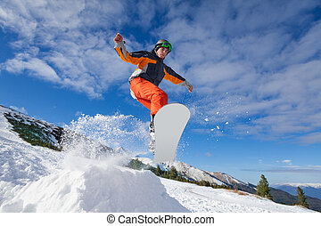 Man jumping with snowboard from mountain hill in winter