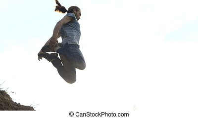 Man jumps in a sand in slow motion outdoors at sunset.