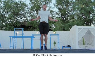 Man jumps on a skipping rope. Slow motion