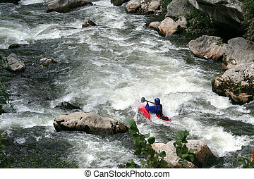 Man kayaking down rapids