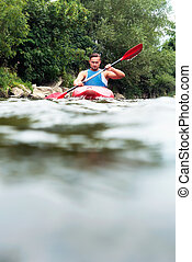 Man kayaking - Surface view of a young man kayaking down a ...