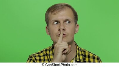 Man keeping a secret or asking for silence, serious face,...