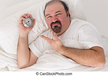 Middle-aged bearded man kept awake by noisy neighbours lying in bed grimacing and pointing to the time on his alarm clock