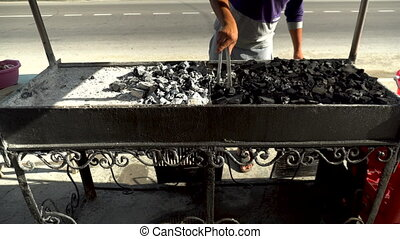 Man kindles coals in a barbecue