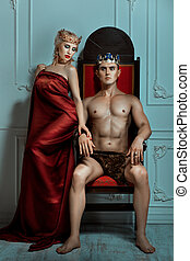 Man king sitting on the throne beside the Queen is a woman. Man is strong and overbearing.