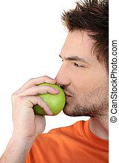 Man kissing a green apple