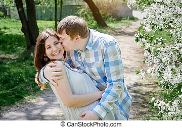 man kissing a woman in the cherry blossoming spring park
