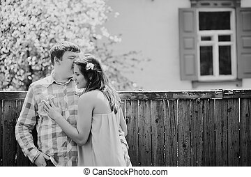 man kissing a woman near the cherry blossoming spring tree