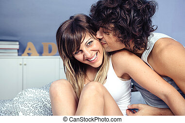 Man kissing and doing tickles to woman laughing