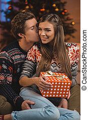 man kissing girlfriend with christmas present