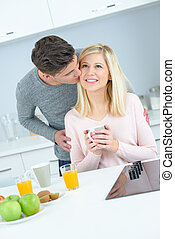 man kissing his girlfriend during the breakfast