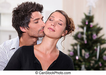 Man kissing his partner in front of a Christmas tree
