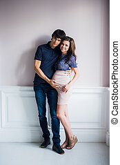 Man kissing his pregnant wife and touching her belly