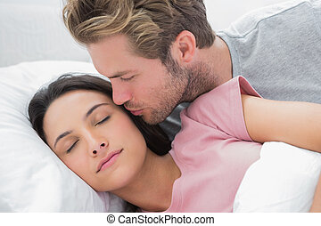 Man kissing his sleeping wife on the cheek
