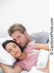 Man kissing his sleeping wife