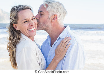 Man kissing his smiling partner on the cheek at the beach