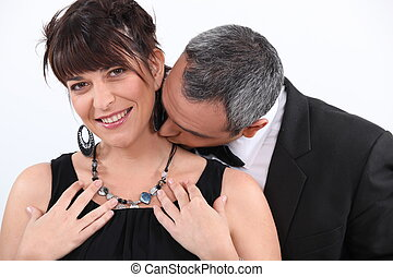man kissing his wife on the neck