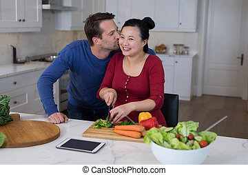 Man kissing the woman while chopping vegetables