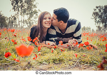 Man kissing woman and she has a toothy smile while they laying on the grass in a field of red poppies