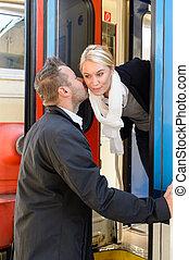 Man kissing woman goodbye on cheek train
