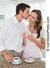 Man kissing woman while having coffee in kitchen
