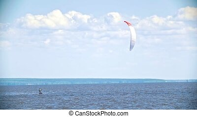 Man kitesurfer on the board flying on the river with sail,...