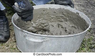 Man knead the concrete in the tub