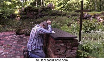 Man kneeling at the altar in outdoor church