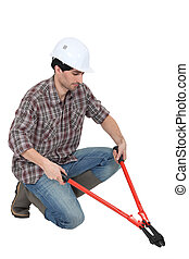 Man kneeling with bolt-cutters