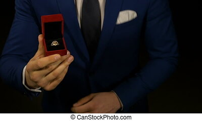 Man kneeling with engagement ring box in hand for marriage...