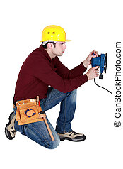 Man kneeling with power sander
