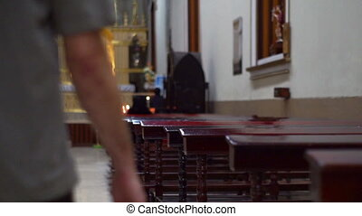 Man walks into the scene of many church benches and a distant altar and kneels on a church pew to worship and pray to his god.