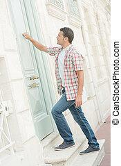 Man knocking at a door arrive