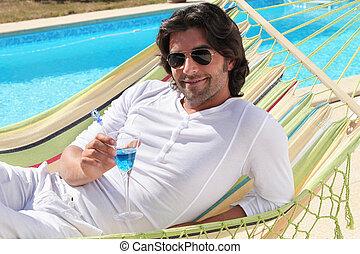 Man laid in hammock enjoying cocktail