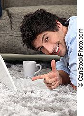Man laid on a carpet with laptop