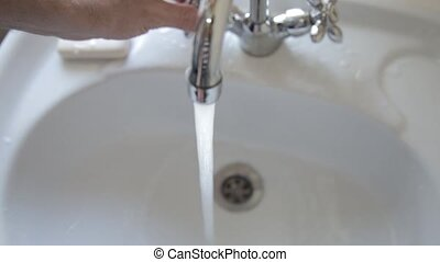 Man lathers and washes his hands. Cleaning Hands with sprays of water. Hygiene