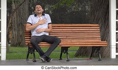 Man Laughing Alone Sitting On Park Bench