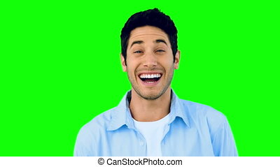 Man laughing at the camera on green