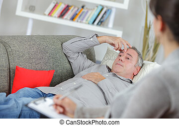 Man layed on couch talking to therapist