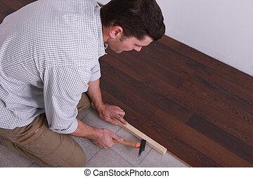 Man laying a hardwood floor