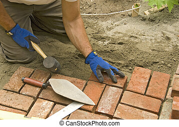 man laying brick patio