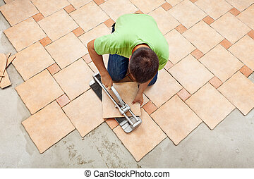 Man laying ceramic floor tiles working with a cutter device...