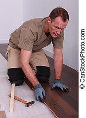 Man laying down flooring