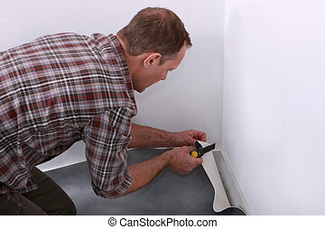 Man laying down linoleum flooring