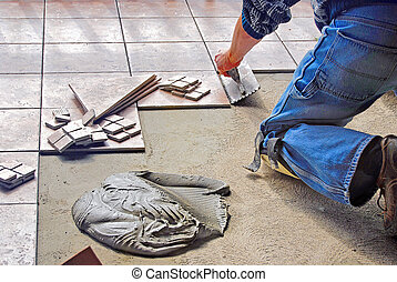 man laying floor tile - Man laying ceramic floor tile with ...