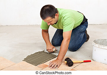Man laying ceramic floor tiles - spreading the adhesive material
