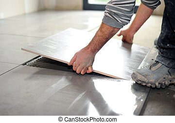 Man laying floor tiles